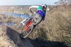 登山车的专业骑自行车者沿岩石地形,背面图乘坐 免版税库存照片