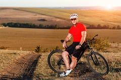 登山车骑马的年轻聪慧的人在秋天风景 图库摄影