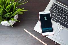 登录在iphone 7屏幕上的Tumblr的按钮在膝上型计算机键盘被安置在EarPods旁边 库存照片