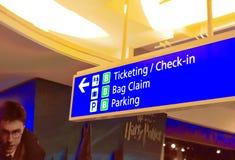 登记和卖票信息标志在哈利波特图象backround的机场 免版税库存图片