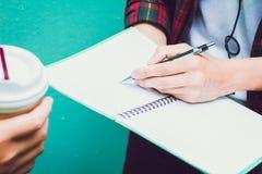 登记概念教育查出的老 两名亚裔妇女一个学生或室友有朋友的 分析作业簿学会的帮助室外,个别辅导书 免版税库存照片
