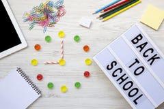 登记概念教育查出的老 九个o在手表的`时钟 时钟由五颜六色的糖果制成,回到学校`词的`在lightbox, st的辅助部件 免版税库存图片