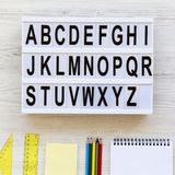 登记概念教育查出的老 信件从A到Z 在lightbox和辅助部件的英语字母表在白色木书桌的研究的,在头顶上 免版税图库摄影