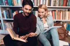 白人和女孩在书架附近在图书馆里 学生是阅读书 免版税库存图片