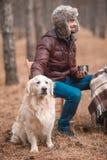 白人坐椅子并且在狗旁边喝一份热的饮料 库存照片