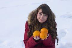 白人妇女举行桔子户外果子冬天 库存图片
