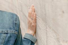 白人妇女手接触墙壁 宗教手指特写镜头在石古老街道墙壁上的 免版税库存照片
