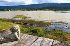 白人妇女雕象有倾向的看的湖 图库摄影