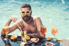 白人肌肉裸体露胸部与在游泳场的鸡尾酒饮料新感觉的 库存图片