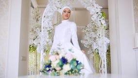 白传统穆斯林的美丽的新娘穿戴与花 股票录像