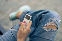 白便携式音乐播放在手中有红色指甲油的 免版税库存图片