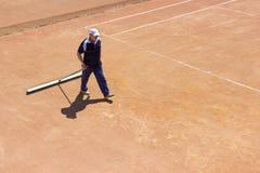 白俄罗斯,米斯克26 05 18 地面网球场的准备 一个人清洗网球场 免版税库存图片