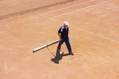 白俄罗斯,米斯克26 05 18 地面网球场的准备 一个人清洗网球场 图库摄影