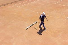 白俄罗斯,米斯克26 05 18 地面网球场的准备 一个人清洗网球场 库存照片