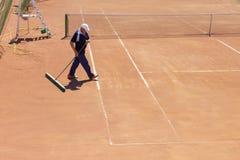 白俄罗斯,米斯克26 05 18 地面网球场的准备 一个人清洗网球场 免版税库存照片