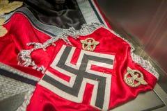 白俄罗斯,米斯克- 2018年5月01日:关闭纳粹Hakenkreuz的十字记号报名参加在状态博物馆的一个红色品牌里面 库存图片