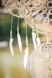 白光羽毛在与透明小珠的螺纹垂悬 从花边的圆的dreamcatchers 免版税库存照片