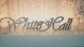 白厅在桌上的题字身分与在婚姻的曲拱的背景的灼烧的蜡烛 股票视频