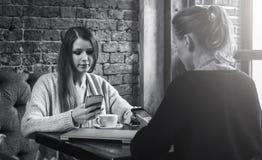黑白图象 坐在咖啡馆在桌上和使用智能手机的两个少妇 免版税库存照片
