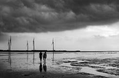 黑白在爱和举行手的浪漫夫妇,他们一起面对一场大风暴 免版税库存照片