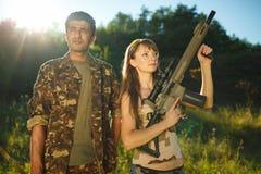 白女孩和一个阿拉伯人伪装的与一个武器在ha 免版税库存照片