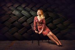 白女孩坐与轮胎后边墙壁的一把椅子  免版税库存照片