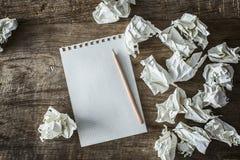 白方块纸、铅笔和被浪费的纸在木后面地面 库存照片