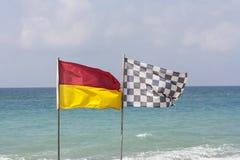 黑白方格的旗子和海浪救生旗子在海滩照片 图库摄影