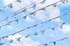 白旗三角形状,反对蓝色多云天空的信号旗对角诗歌选  城市街道假日,节日 免版税库存图片