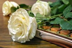 白玫瑰和巧克力作为礼物 免版税库存照片