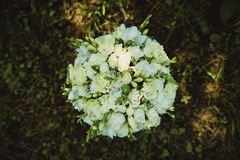 白玫瑰和金刚石美妙地装饰的婚姻的花束  免版税库存照片