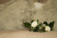 白玫瑰在米黄床顶部的花束细节与蓬松枕头 库存照片