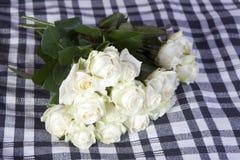 白玫瑰在黑白的方格的格子花呢披肩说谎 免版税图库摄影