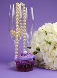 白玫瑰婚礼花束用紫色杯形蛋糕和珍珠在香槟玻璃-垂直。 免版税库存照片