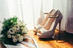 白玫瑰婚礼花束的特写镜头侧视图在米黄婚礼高跟鞋附近被安置的在窗口附近 免版税图库摄影