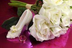 白玫瑰婚姻的新娘花束与鞋子和圆环的。 免版税库存图片