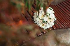 白玫瑰新娘花束与一条金丝带的在一条棕色长凳 免版税库存照片