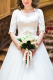 白玫瑰的婚礼花束的特写镜头视图在新娘的手上 免版税库存照片