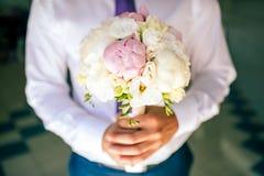 给白玫瑰的花束男性手 库存照片
