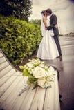 白玫瑰花束反对一对亲吻的新婚佳偶夫妇的背景的 免版税库存图片