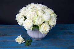 白玫瑰豪华的花束在蓝色木桌上站立 图库摄影