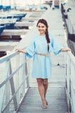 白白种人深色的妇女画象有被晒黑的皮肤的在海滨的蓝色礼服湖岸与游艇小船 库存图片