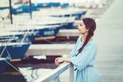 白白种人深色的妇女画象有被晒黑的皮肤的在海滨的蓝色礼服湖岸与游艇小船 免版税库存图片