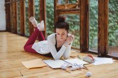 白白种人年轻深色的女学生,女性艺术家,坐在学院大学图画速写的地板 免版税图库摄影