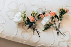 白百合和桃子玫瑰花束在床上 免版税库存照片