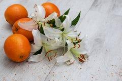白百合和花粉在地板上用桔子 免版税库存照片