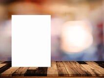 白皮书在木桌上的海报倾斜与在c的被弄脏的内部 库存照片
