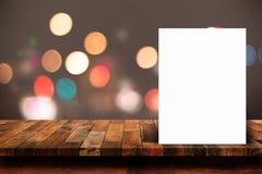 白皮书在木桌上的海报倾斜与bokeh摘要光 库存图片