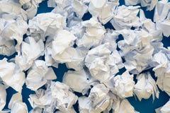 白皮书球被弄皱的板料  很多垃圾纸 蓝色 免版税库存图片
