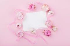 白皮书空白和春天在桃红色书桌上从上面开花婚姻的大模型或贺卡的在妇女天 花卉框架构成系列 免版税库存图片